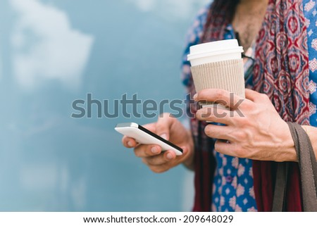 Close-up of male hand holding coffee cup and using smartphone - stock photo