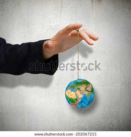 Close up of male hand holding Earth planet on rope. Elements of this image re furnished by NASA - stock photo