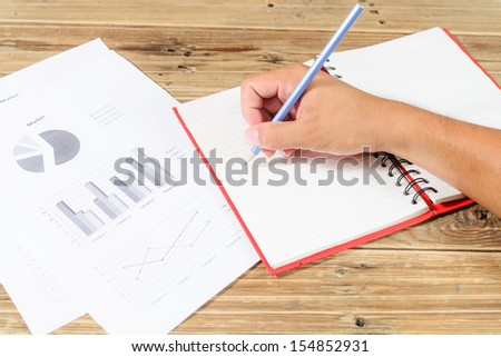 Close-up of male hand holding pencil over notebook
