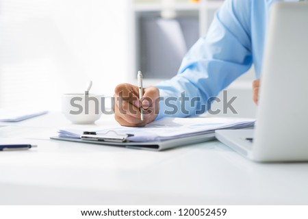 Close-up of male hand making notes in office - stock photo