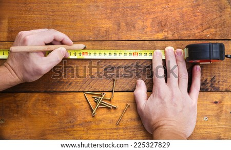 Close up of male hand measuring and marking wood flooring with tape measure - stock photo