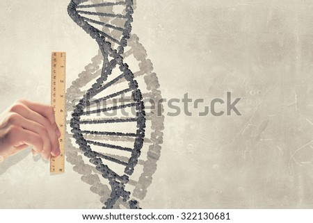 Close up of male hand measuring DNA molecule with ruler - stock photo