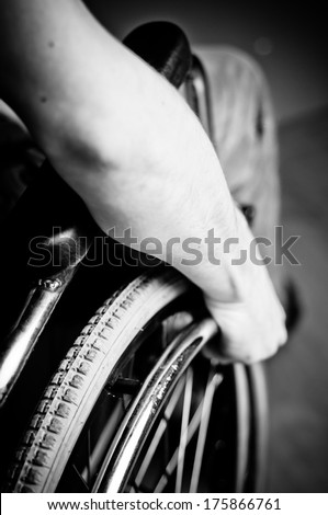 Close-up of male hand on wheel of wheelchair - stock photo