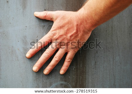 Close Up of Male Hand Pressing Against Industrial or Construction Material Grey Background  - stock photo