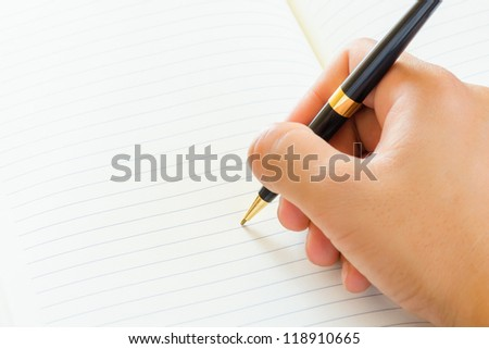 Close up of male hand signing a contract on blank white paper. - stock photo
