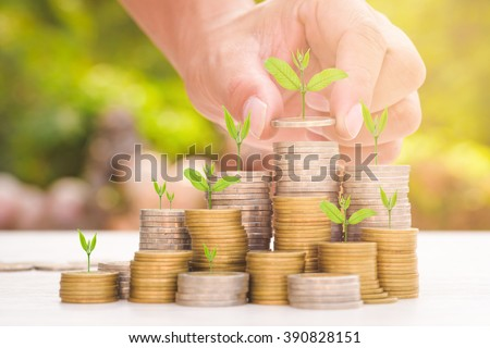 Close up of male hand stacking gold coins with green bokeh background ,Business Finance and Money concept,Save money for prepare in the future.Trees growing on coin - stock photo