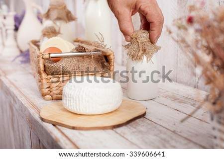 Close up of male hand touching a bottle on milk. There are a basket of eggs and cheese on the table - stock photo
