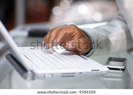 Close-up of male hand typing on white laptop computer - stock photo