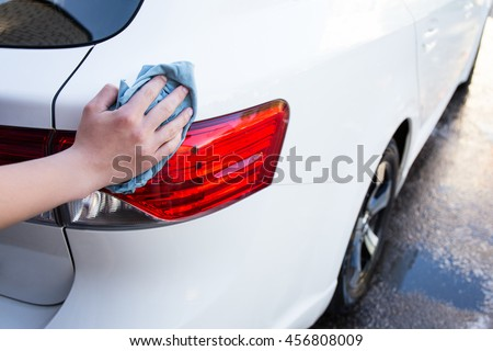 close up of male hand washing car rear lights with microfiber cloth - stock photo