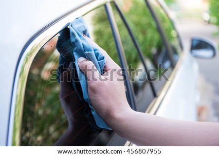 close up of male hand washing car window with microfiber cloth - stock photo