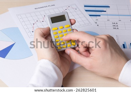 close up of male hands accounting something with calculator - stock photo