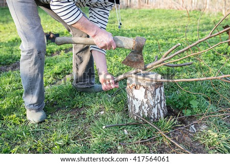 Close-up of male hands chopping firewood, tree branch on stump with old rusty axe