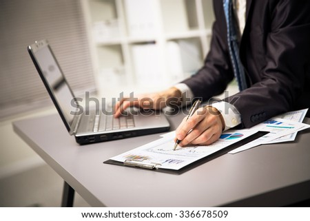 Close up of male hands doing paperwork with pen and laptop.