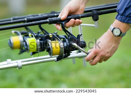Close up of male hands holding fishing rod - stock photo
