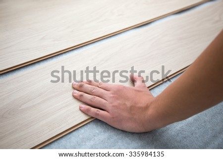 close up of male hands installing new laminated wooden floor - stock photo