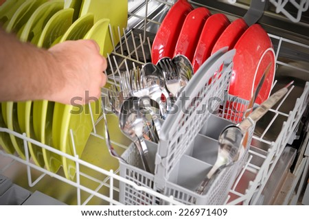 close-up of male hands loading dirty dishes to the dish washing machine  - stock photo