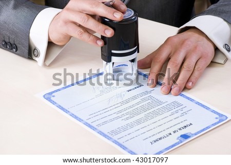 close-up of male hands of the notary stamp on the power of attorney. Document and signature of the fictitious - stock photo