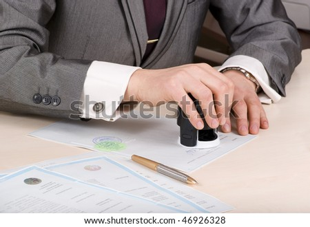 close-up of male hands of the seal on the sertificate - stock photo