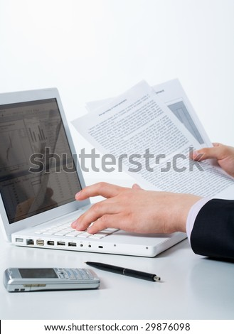 Close-up of male hands pressing keys of computer board and holding papers