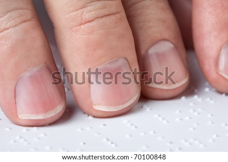 Close up of male hands reading braille text - stock photo