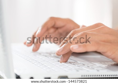 Close up of male hands typing on a laptop - stock photo