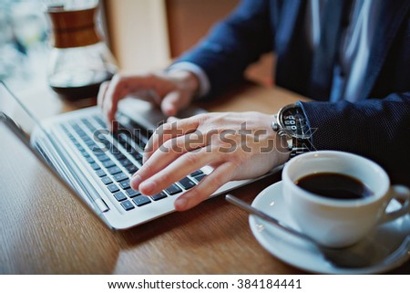 Close-up of male hands typing on laptop during coffee break - stock photo