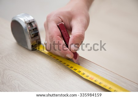 close up of male hands with measuring tape and new laminated wooden floor - stock photo
