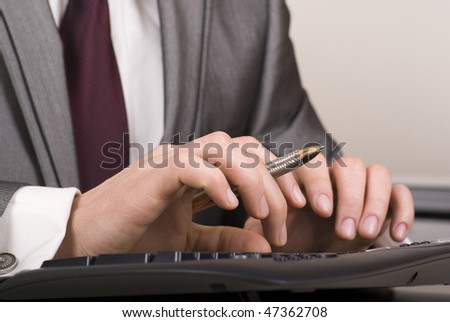 Close-up of male hands with pen typing on black computer keyboard