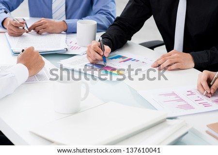 Close-up of male hands working with business diagrams at the meeting - stock photo