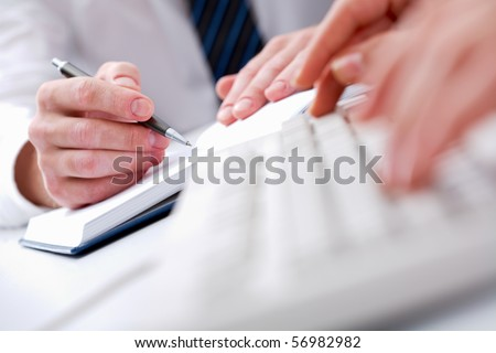 Close-up of male hands writing in notepad with typing secretary hands in front of him - stock photo