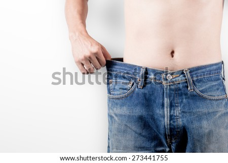 Close-up of male in jeans showing successful weight loss,on white background, diet concept
