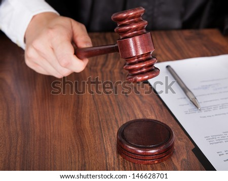 Close-up Of Male Judge Hand Striking The Gavel In A Courtroom - stock photo
