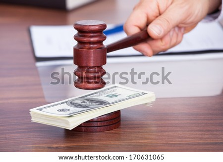 Close-up Of Male Judge Hitting Mallet On American Dollars Banknote - stock photo