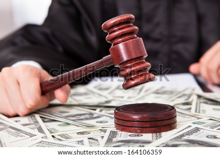 Close-up Of Male Judge Hitting Mallet On Banknote - stock photo