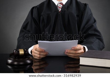 Close-up Of Male Judge Reading Paper In Courthouse - stock photo