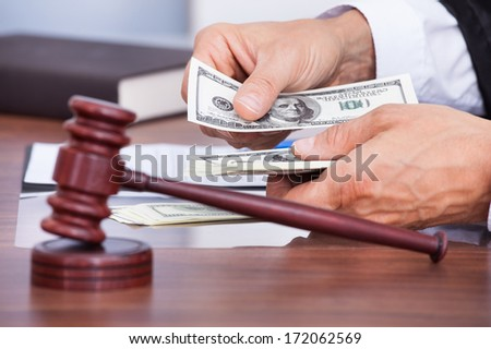 Close-up Of Male Judge's Hand Counting Banknote In Front Of Mallet - stock photo