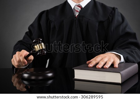 Close-up Of Male Judge With Gavel And Book At Desk - stock photo