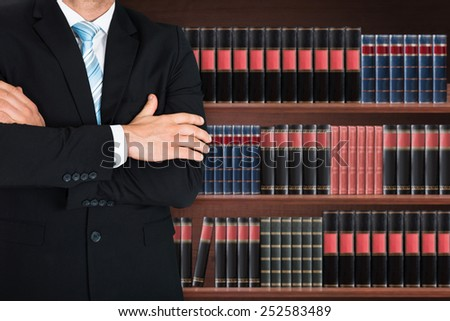 Close-up Of Male Lawyer With Arm Crossed Standing In Front Of Book Shelf - stock photo