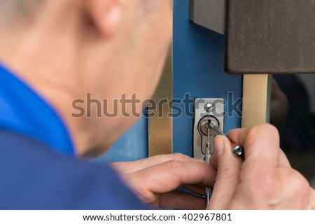 Close-up Of Male Lockpicker Hand Fixing Door Handle At Home - stock photo