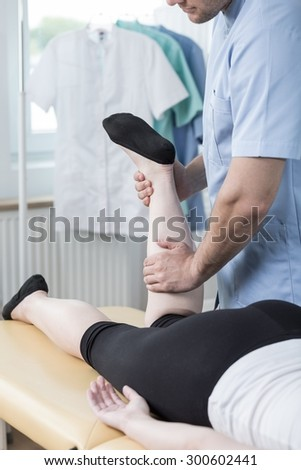 Close-up of male physiotherapist doing functional massage - stock photo
