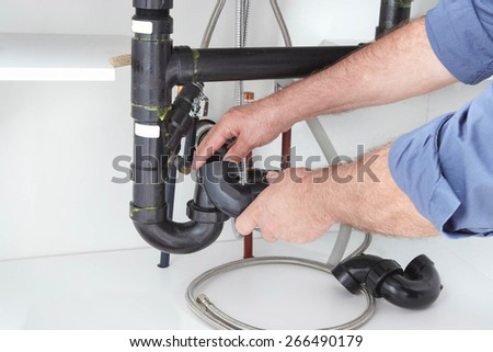Close Up of Male Plumber Fixing a Sink in Bathroom - stock photo