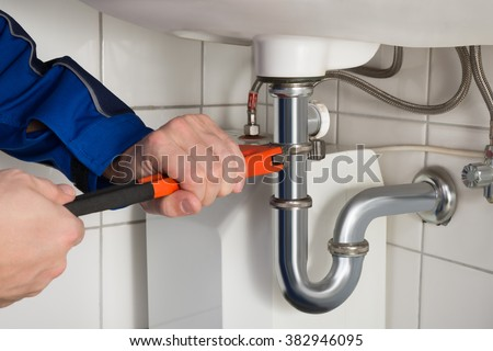 Close-up Of Male Plumber Repairing Sink In Bathroom - stock photo