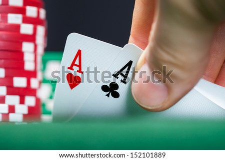 Close-up of male poker player lifting the corners of two cards - stock photo