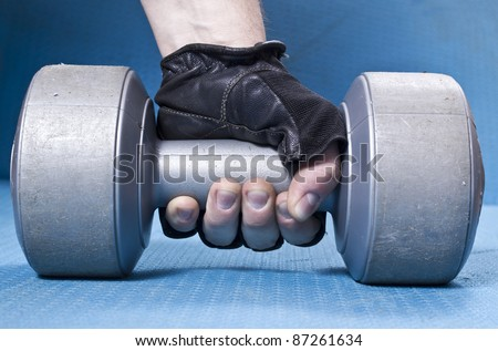 Close-up of male's hand with metal weight - stock photo