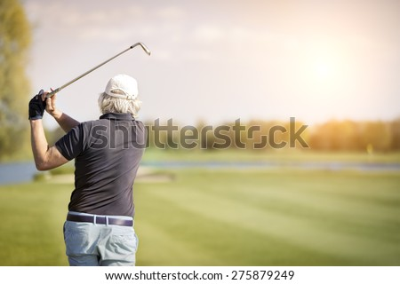 Close up of male senior golf player swinging golf club, with empty copyspace for text. - stock photo