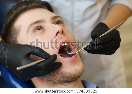 Close-up of male with open mouth during oral checkup at the dentist.Dentist - stock photo