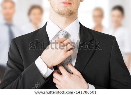 close up of man adjusting his tie - stock photo