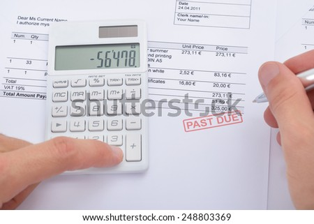 Close-up Of Man Analyzing Past Due Statement Using Calculator - stock photo