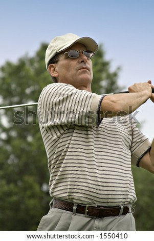 Close up of man as golf swing is completed. - stock photo