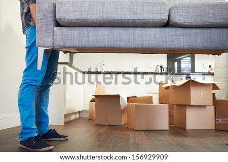 Close Up Of Man Carrying Sofa As He Moves Into New Home - stock photo